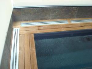 Dettaglio di teak posato con clip e fresatura simmetrica. Bordo  piscina di abitazione privata.